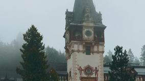 Peles Castle and a Misty Pine Tree Forest in Sinaia, Transylvania, Romania - Close-up Front View. A tilting ultra close-up front view shot of the Neo-Renaissance stock video footage
