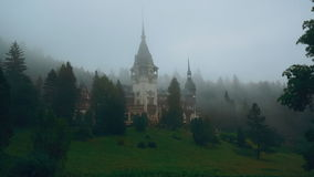 Peles Castle and a Misty Pine Tree Forest in Sinaia, Transylvania, Romania - East View stock video footage