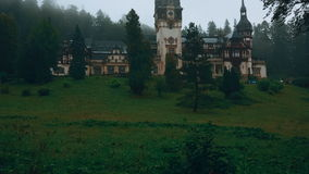 Peles Castle and a Misty Pine Tree Forest in Sinaia, Transylvania, Romania - Front View stock video footage