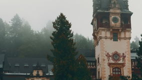 Peles Castle and a Misty Pine Tree Forest in Sinaia, Transylvania, Romania - Panoramic East View stock footage