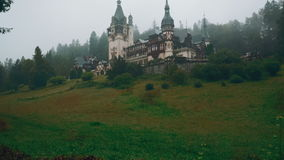 Peles Castle and a Misty Pine Tree Forest in Sinaia, Transylvania, Romania - Ultra Wide Angle Front View stock video footage