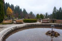 Peles castle ornamental garden, Sinaia, Romania. Landmark of Car. Pathian mountains in Europe. Fountain in foreground royalty free stock images