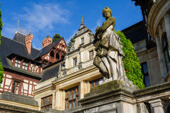 Peles Castle in Sinaia, Romania. Statue in front of beautiful Peles castle and ornamental garden in Sinaia, Romania, between Valachia and Transylvania Royalty Free Stock Photos