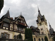 Peles Castle. In Transylvania, Romania on a cloudy day with a view of towers, the façade, walls and clocks stock image