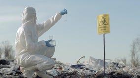 Peligro biológico, químico de Hazmat en la ropa protectora que recoge la muestra infectada de la basura en el tubo de ensayo para almacen de metraje de vídeo