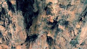 Peligroso subiendo para arriba el acantilado de piedra de la roca de la arena con el bosque de color verde oscuro en la isla de S metrajes
