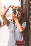 Pelirrojo bonito que toma una imagen con la cámara retra Foto de archivo