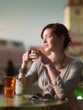 Pelirrojo hermoso bebiendo un cofee en la ciudad Imagen de archivo libre de regalías
