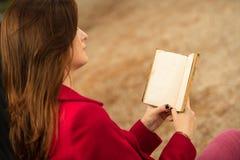 Pelirrojo hermoso que lee un libro Fotografía de archivo