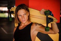 Pelirrojo joven atractivo y hombre de pelo largo con el tatuaje que celebra un longboard Foto de archivo