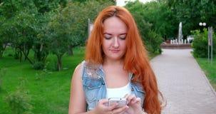 Pelirrojo que manda un SMS en un smartphone Trabajo de las mujeres almacen de video