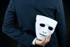 Pellame dell'uomo d'affari la maschera bianca nella mano dietro la sua parte posteriore sulla b fotografia stock libera da diritti
