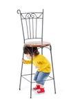 Pellami del ragazzino sotto l'alta sedia in ferro battuto Fotografie Stock Libere da Diritti