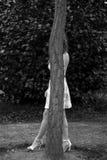 Pellami della donna dietro un albero immagine stock libera da diritti
