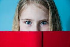 Pellami della ragazza della scuola dietro il libro Chiuda sul ritratto, foto dello studio Fotografia Stock Libera da Diritti
