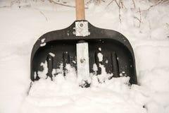 Pelle à neige dans la neige sur un fond d'un mur de briques Photo stock