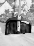 Pelle à neige dans la neige sur un fond d'un mur de briques Images libres de droits
