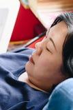 Pelle bianca asiatica delle donne 40s che pensa sul sofà Immagine Stock