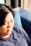 Pelle bianca delle donne 40s dell'Asia che pensa sul sofà Fotografie Stock