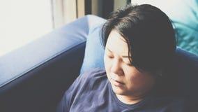 Pelle bianca delle donne 40s dell'Asia che pensa sul sofà Fotografia Stock