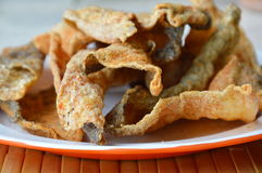 Pelle fritta croccante del pesce con condimento sul piatto Immagini Stock Libere da Diritti