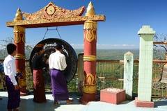 Pellegrini vicino al gong Monastero di Taung Kalat Supporto Popa Regione di Mandalay myanmar immagini stock
