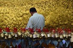 Pellegrino che incolla le stagnole di oro su roccia dorata alla pagoda di Kyaiktiyo, Myanmar con la fila di piccole campane in pr Fotografia Stock
