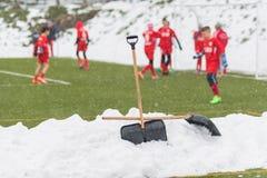 Pelles dans la pile de la neige après nettoyage de la neige du football Photo libre de droits
