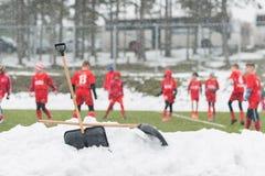Pelles dans la pile de la neige après nettoyage de la neige du football Photographie stock