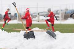 Pelles dans la pile de la neige après nettoyage de la neige du football Photo stock