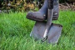 Pelles et bottes en caoutchouc dans le jardin photos libres de droits