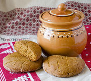 Pellet and a clay jug. Round bread cakes made of rye flour, clay jug on the table Royalty Free Stock Images