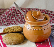 Pellet and a clay jug. Round bread cakes made of rye flour, clay jug on the table Royalty Free Stock Image