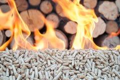 Pellets- Biomas. Pine pellets in flames- behind flames ara fire wood Royalty Free Stock Image