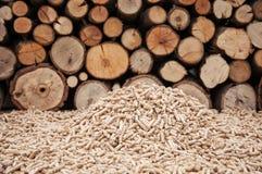 Pellets- Biomas. Pine pellets infront a wall of firewoods Stock Photos