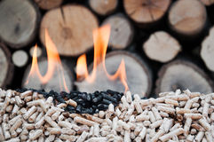Pellets- Biomass. Pine pellets in flames- selective focus on the heap Stock Photo