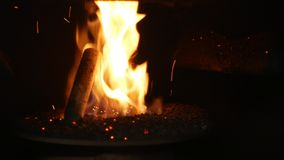 Pellets fire burn with spruce sawdust into the delivery strew bio wooden pallets to industrial modern boiler, sparks fly