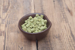 Pellets of hops. On wooden table Royalty Free Stock Photography