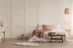 Pelliccia e panchetto di legno davanti al letto con la coperta nell'interno bianco della camera da letto con la lampada fotografia stock libera da diritti