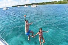 Pelliculage joyeux de couples tout en sautant à la mer Photographie stock libre de droits