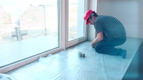 Pellicule de polyéthylène de configuration de travailleur de la construction sur le plancher banque de vidéos