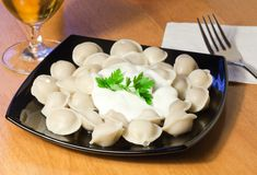 Pelmeni (meat dumplings) with sour cream Stock Image
