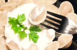 Pelmeni (meat dumplings) with sour cream Stock Photo