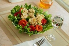 Pelmeni mit Fleisch werden durch Gemüse verziert Stockfotos