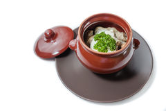 Pelmeni and mushrooms in a clay pot Stock Photo