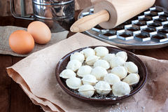 Pelmeni and round form for a molding of pelmeni on a wooden tabl Royalty Free Stock Image
