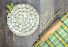 Pelmeni ruso de las bolas de masa hervida de la carne con el rodillo en fondo de madera Fotografía de archivo