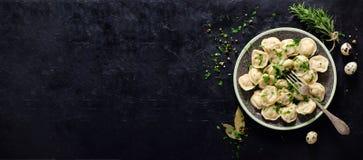 Pelmeni russo tradizionale, ravioli, gnocchi con carne su fondo concreto nero Prezzemolo, uova di quaglia, pepe Fotografia Stock Libera da Diritti