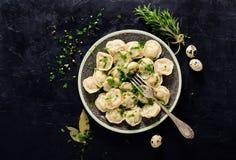 Pelmeni russo tradizionale, ravioli, gnocchi con carne su fondo concreto nero Prezzemolo, uova di quaglia, pepe Fotografia Stock