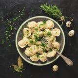 Pelmeni russo tradizionale, ravioli, gnocchi con carne su fondo concreto nero Prezzemolo, uova di quaglia, pepe Immagine Stock